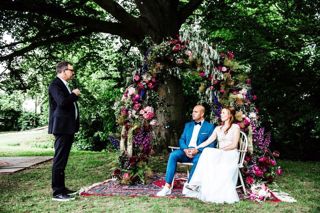 Hochzeitspaar sitzt vor bunt geschmücktem Baum